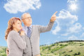 Mature couple standing and looking close together with blue sky in the background Stock Photos