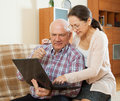 Mature couple studying laptop elderly gray haired men and women working at at home Stock Images