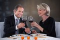 Mature couple toasting wine happy in a elegant restaurant Stock Images