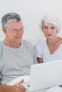 Mature couple using a laptop in bed Royalty Free Stock Photography