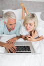 Mature couple using laptop in bed relaxed at home Stock Photos