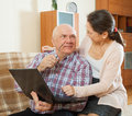 Mature couple using laptop at home middle aged men and women sitting on couch with Royalty Free Stock Photography