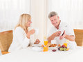 Mature couple using and pointing at a tablet computer while enjoying their healthy breakfast attractive of fresh fruit eggs orange Stock Photo