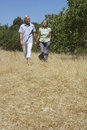 Mature couple walking in field full length of a holding hands and Stock Photos