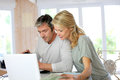 Mature couple working on laptop planning vacation trip with map and Stock Photo