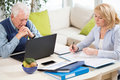 Mature couple working together at home Stock Photos