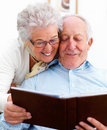 Mature couplel ooking at photo album together Stock Photo