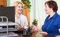 Mature doctor consulting female patient smiling in office Royalty Free Stock Images