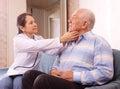 Mature doctor examining senior man men at home Stock Photo