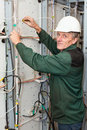Mature electrician working in hard hat with cables Royalty Free Stock Photo