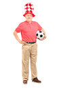 Mature fan with hat holding a soccer ball full length portrait of on white background Stock Photos