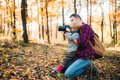 Picture : A mature father and a toddler son in an autumn forest, taking pictures with a camera. dark  in