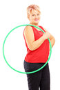 Mature female athlete holding a hula hoop and looking at camera isolated on white background Royalty Free Stock Image