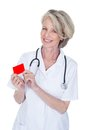 Mature female doctor holding visiting card over white background Stock Image