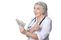 Mature female doctor with money Royalty Free Stock Photo