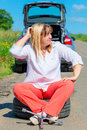 Mature female driver sitting in the spare wheel on a sunny day Royalty Free Stock Image