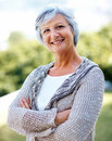 Mature female standing confidently in the park Stock Photography