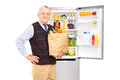 Mature gentleman holding a paper bag in front of refrigerator Stockfotos
