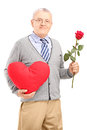 Mature gentleman holding a red heart and flower isolated on white background Stock Photography