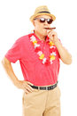 Mature gentleman with lei smoking a cigar and looking at camera isolated on white background Stock Images