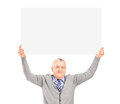 Mature gentleman sitting and holding a blank panel above his hea head isolated on white background Stock Photo