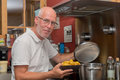 Mature handsome man cooking in home kitchen Royalty Free Stock Photo