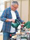 Mature handy man using an electric  saw Stock Photography