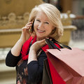 Mature happy woman with shopping bags blonde calling by phone Stock Photography