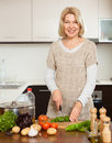Mature housewife cooking with veggy lunch in kitchen Stock Photos