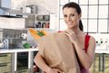 Mature housewife in kitchen at home holding shopping bad smiling Stock Images