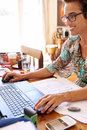 Mature independent business woman busy doing her bookkeeping from home Royalty Free Stock Photo