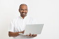 Mature indian man using laptop looking at side portrait of casual business computer and smiling standing on plain background with Royalty Free Stock Photos