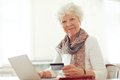 Mature lady with credit card shopping online smiling holding a in front of her laptop Royalty Free Stock Photos