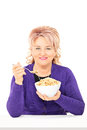 Mature lady eating cereal from a bowl seated on table isolated white background Stock Photos