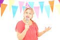 Mature lady with party hat singing on microphone at a birthday p isolated white background Stock Photo