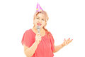 Mature lady with party hat singing on microphone isolated white background Stock Image