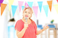 Mature lady with party hat singing on microphone at party a birthday Stock Images