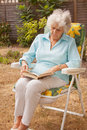 Mature Lady Reading In The Garden Royalty Free Stock Photos
