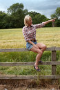 Mature lady sitting on a fence pointing to her left Royalty Free Stock Photography
