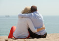 Mature lovers sitting on beach romantic at seashore and enjoying the view Stock Photography