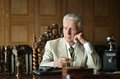 Mature male mafia boss on the table with gun Royalty Free Stock Images