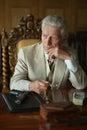 Mature male mafia boss on the table with gun Stock Photo