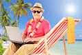 Mature male tourist sitting on a sun lounger and working laptop tropical beach with palm trees Stock Image