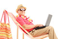 Mature male tourist on a sun lounger with a laptop isolated white background Stock Photo