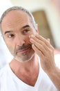 Mature man applying cream to look after skin in front of mirror cosmetics Stock Image
