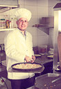 Mature man baking pizza in restaurant Royalty Free Stock Photo