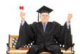 Mature man celebrating his graduation seated on wooden bench isolated white background Royalty Free Stock Photography