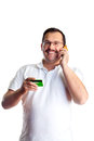 Mature man doing some telephone banking and giving the bank his debit card number isolated on white background Stock Photo