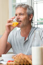 Mature man drinking orange juice a glass of at breakfast Royalty Free Stock Photography