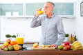 Mature man drinking orange juice in the kitchen freshly squeezed Stock Images